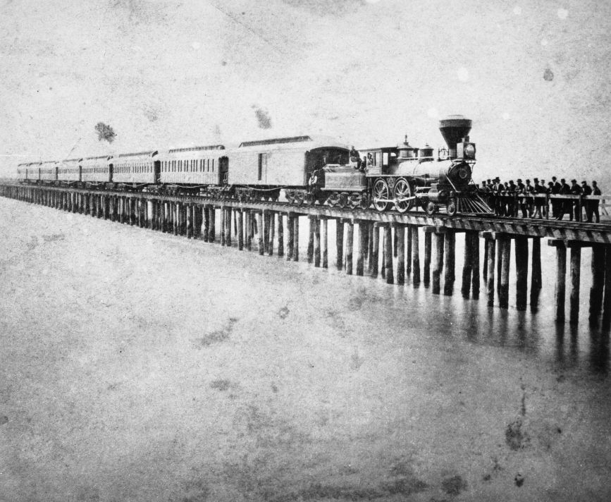 Passenger train of the Central Pacific Railroad on the Oakland Wharf ca. 1870