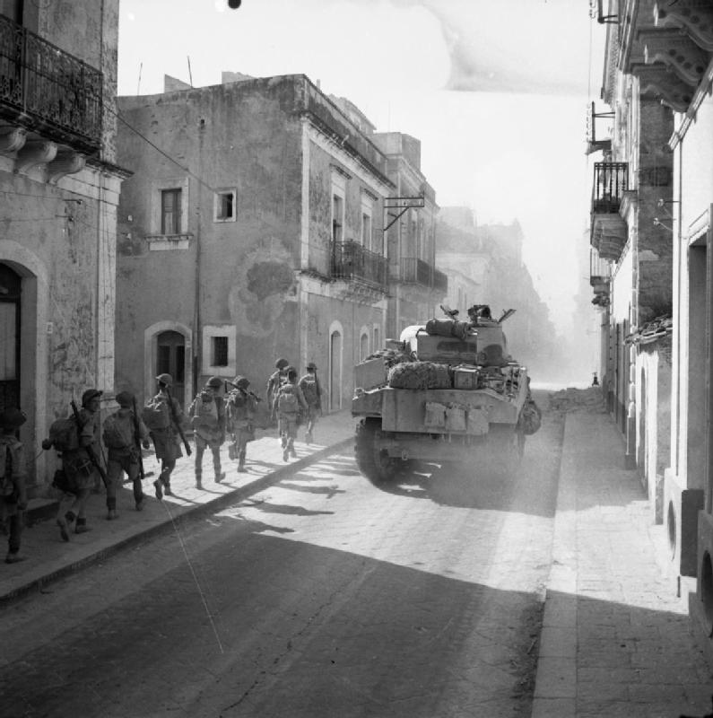 A Sherman tank and infantry advance through the town of Carlentini, 15 July 1943.